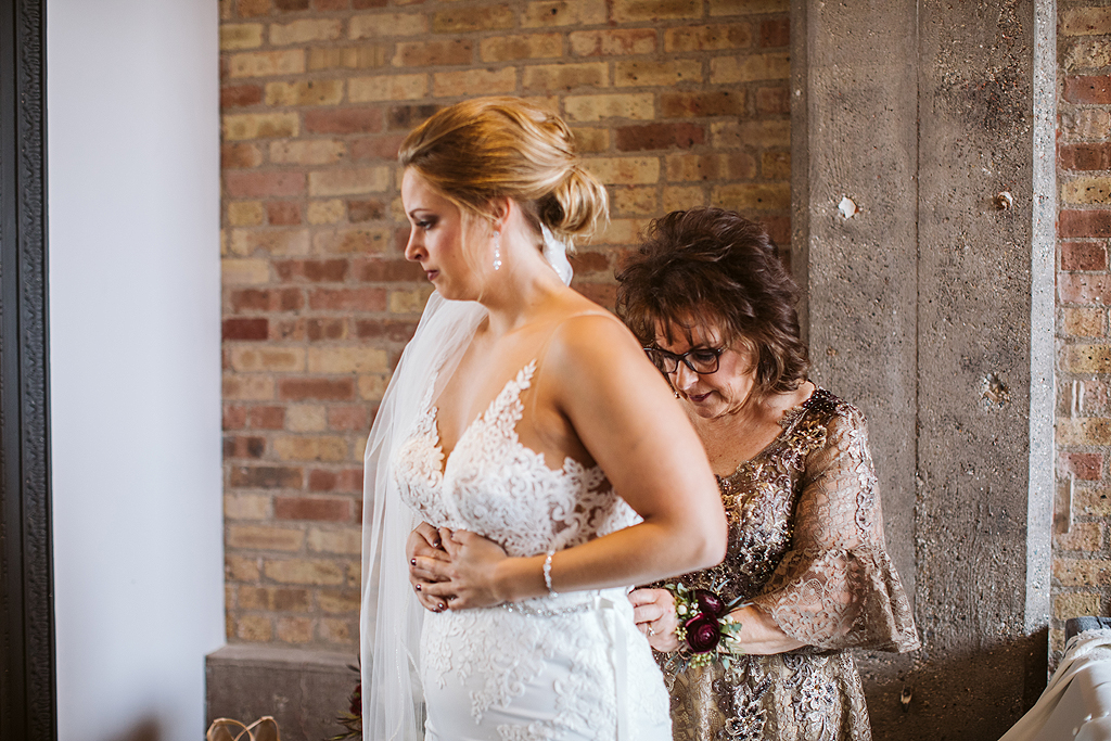 mother helping her daughter into bridal dress