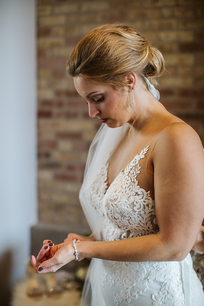 bride putting on bracelet