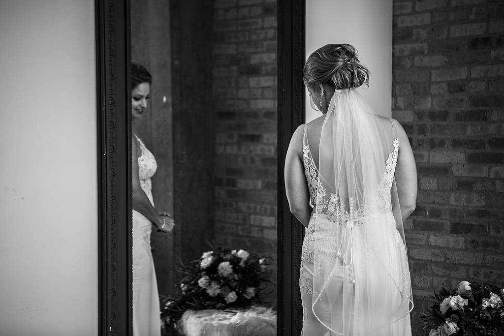 bride looking into a mirror in black and white