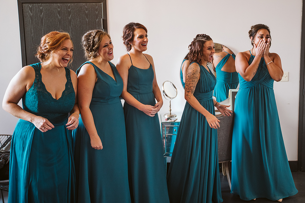 bridesmaids seeing a bride and smiling