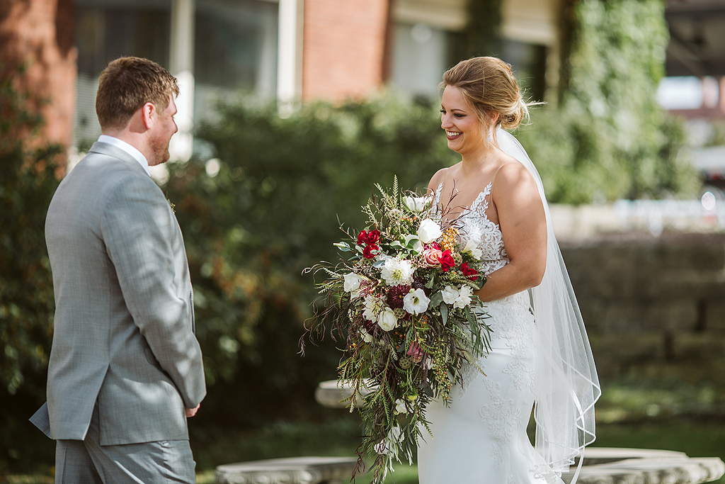 bride and groom smiling while holding flowers