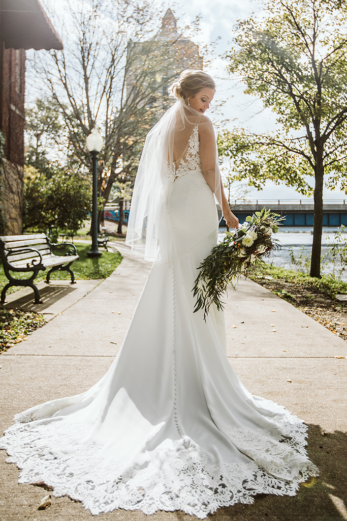 bride with her dress and flowers along the rock river in rockford il