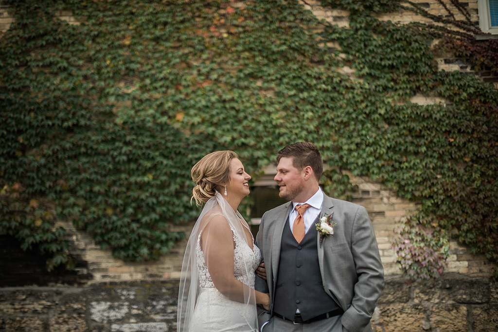 bride and groom along brick wall with ivy