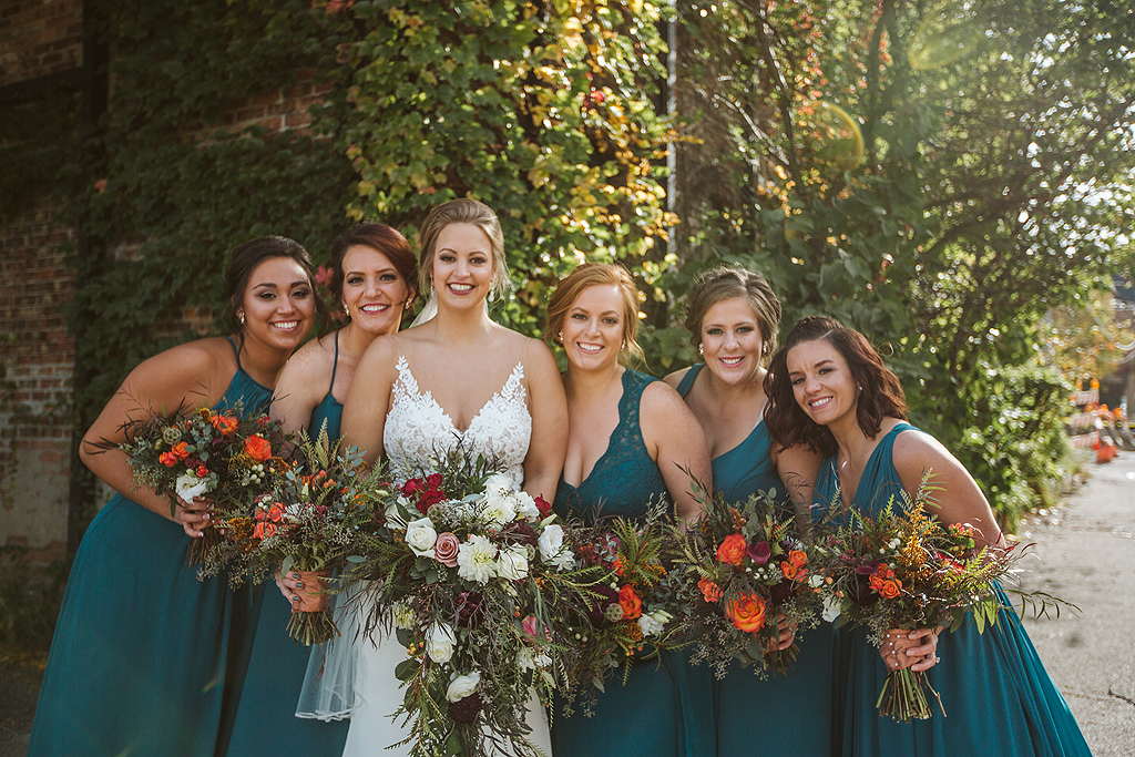 bride and bridesmaids with flowers smiling