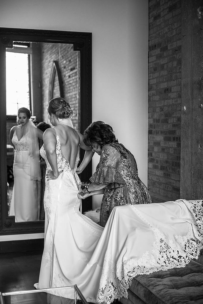 mom helping bride into dress