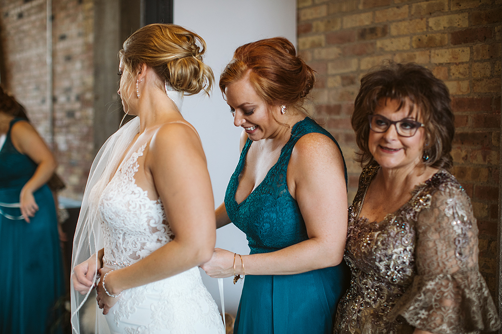 sister and mom helping bride with dress