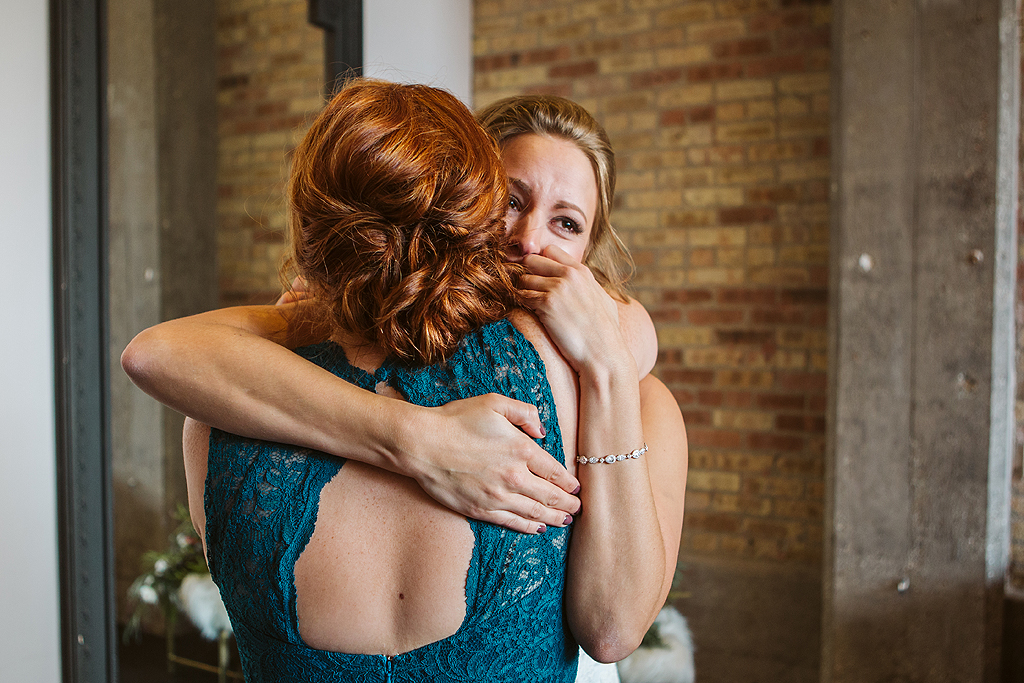 bride hugging sister on wedding day