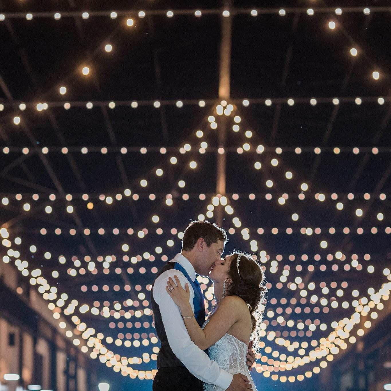Wedding couple kissing under lights at the ironworks hotel in beloit wisconsin