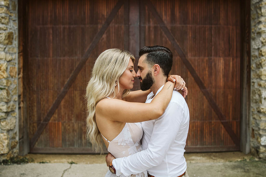 couple kissing in front of old wooden door in rockford illinois
