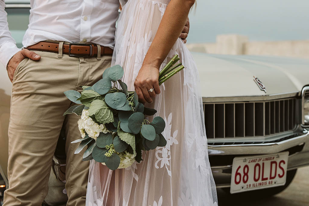 couple with fresh cut flowers and classic car