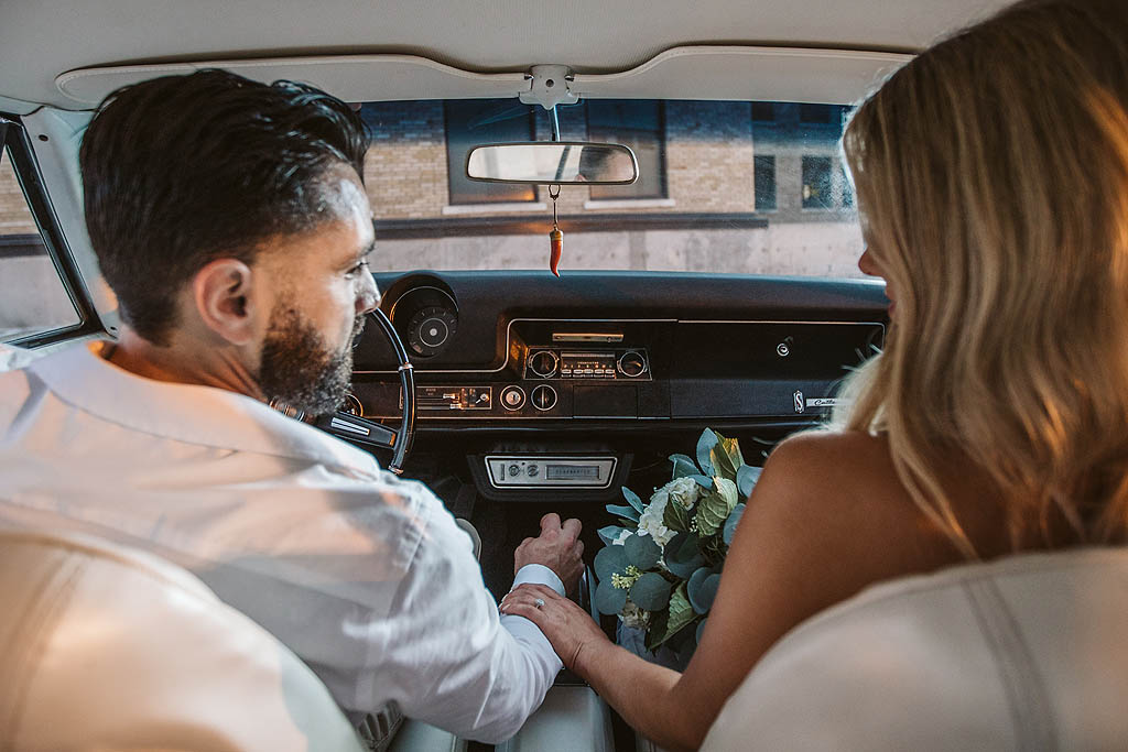 couple holding hands in classic car looking at each other