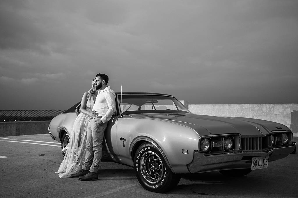 engaged couple standing in front of classic car in rockford illinois