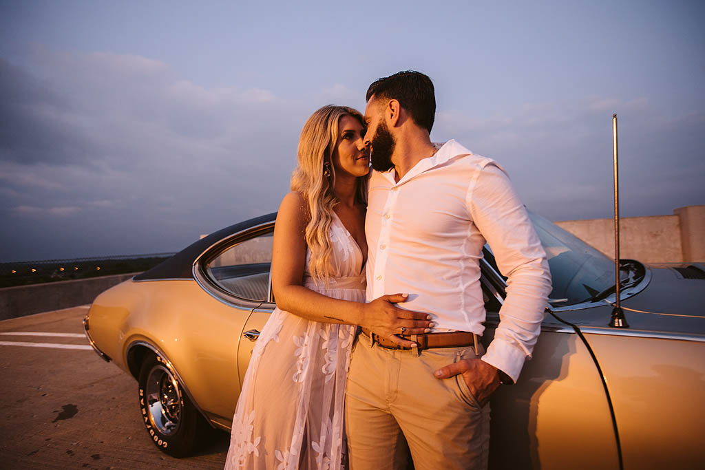 Engaged couple in front of classic car at sunset in rockford illinois