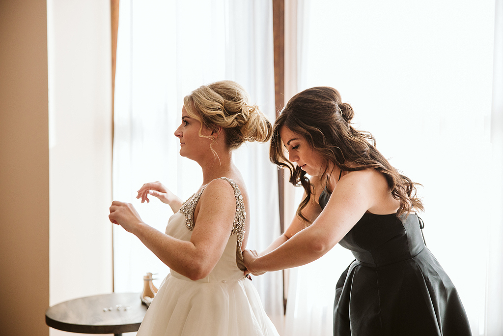 maid of honor helping bride in dress in the bridal suite at The Haight in Elgin Illinois