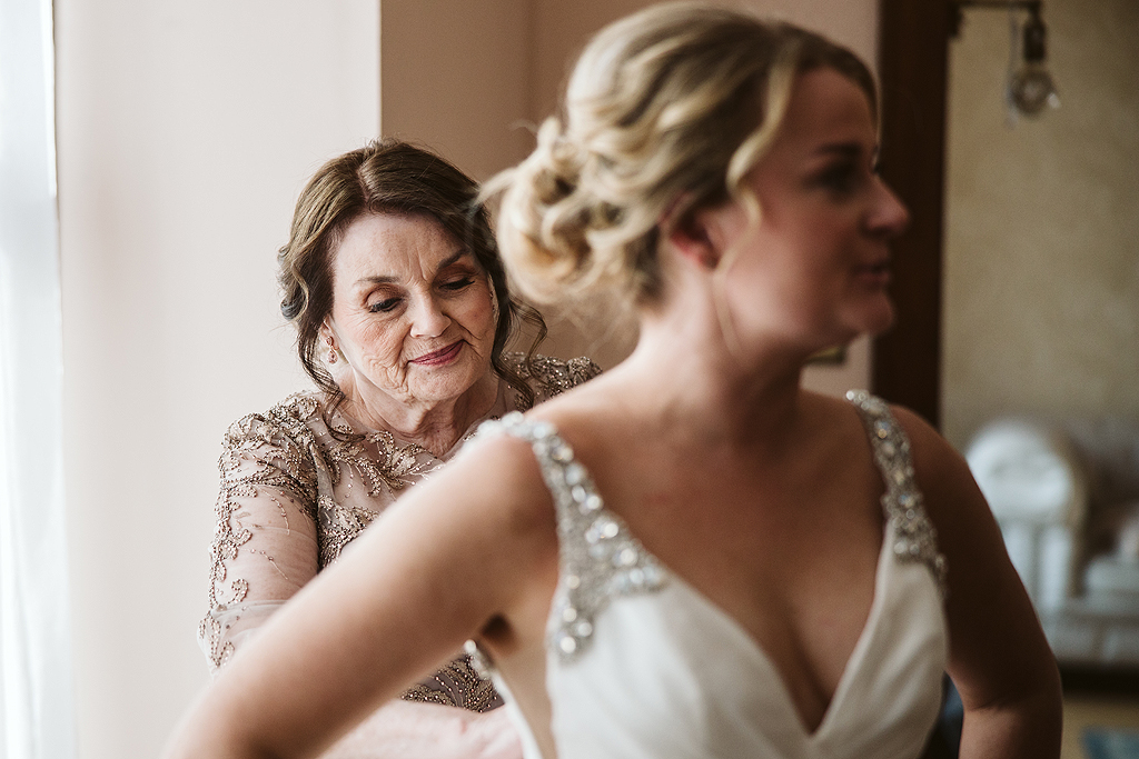 brides mother smiling while helping bride into dress