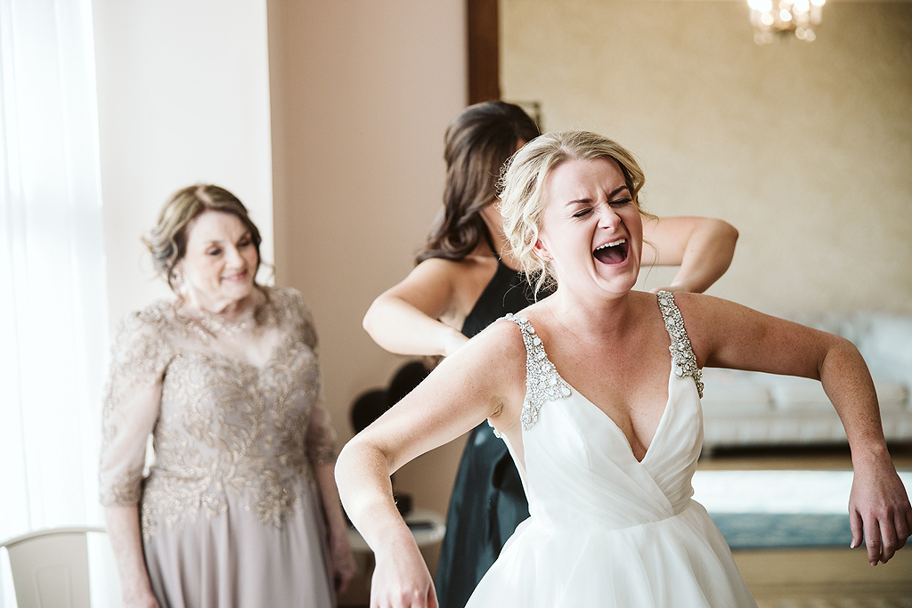 bride laughing while getting ready on her wedding day