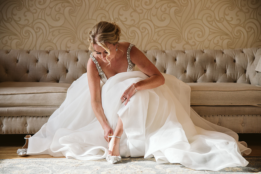 bride putting her shoes on in the bridal suite at The Haight in Elgin Illinois
