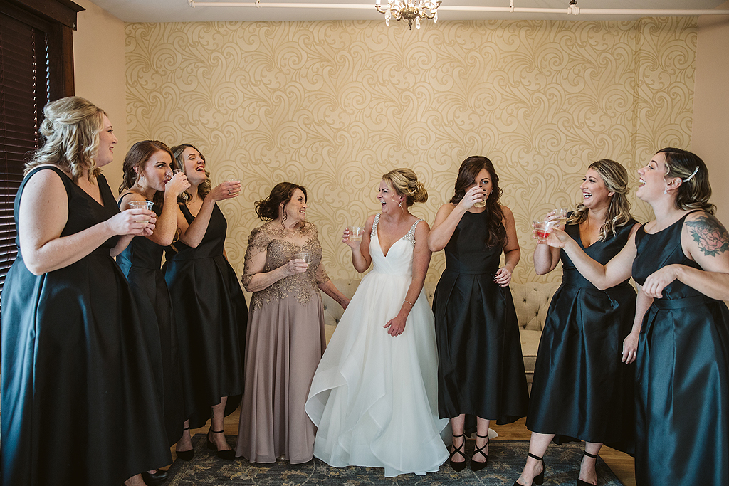 bride and her bridesmaids drinking and laughing in the bridal suite at The Haight in Elgin Illinois