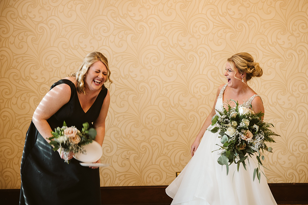 bride and bridesmaid laughing in The Haight in Elgin Illinois