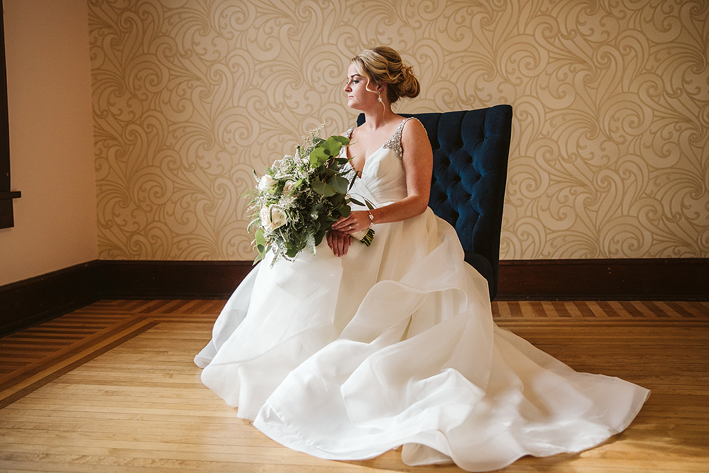 bride sitting on blue chair with her bouquet