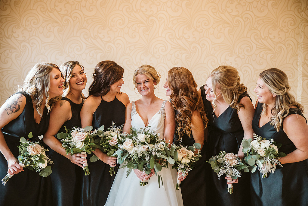 bride and all of her bridesmaids laughing in the bridal suite at The Haight in Elgin Illinois