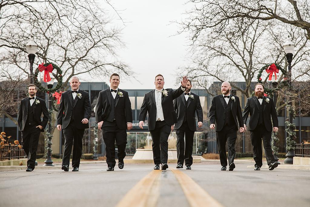 groom walking with groomsmen in downtown elgin illinois
