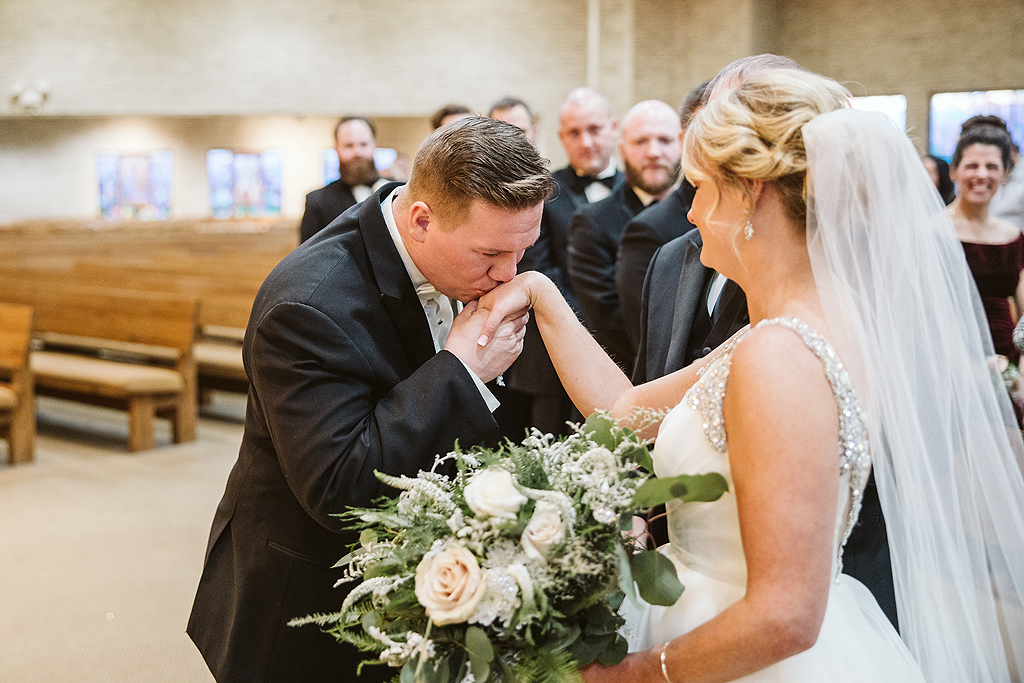 groom kissing brides hand during wedding ceremony