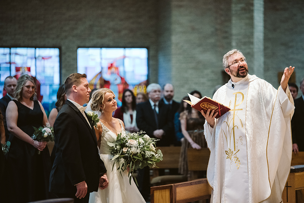 bride and groom looking at priest during their wedding