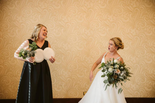 Bride laughing at her Bridesmaid