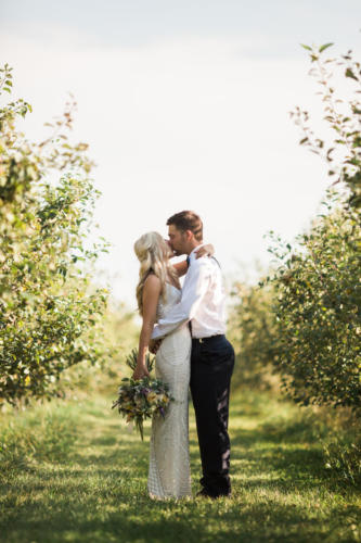 Bride and Groom kissing in orchard at Orchard Ridge Farms the Pavilion in Rockton Illinois