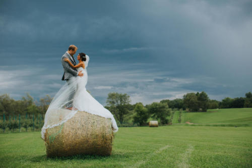 Bride and Groom standing on hay bale at Orchard Ridge Farms the Pavilion in Rockton Illinois