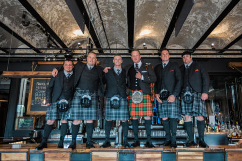 groom and groomsmen with kilts at prairie street brewing company