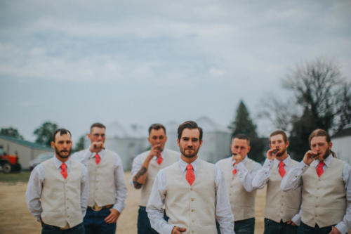 groom and groomsmen smoking cigars on a wedding