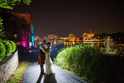 bride and groom night time photograph at prairie street brewing company with rockford illinois in the background