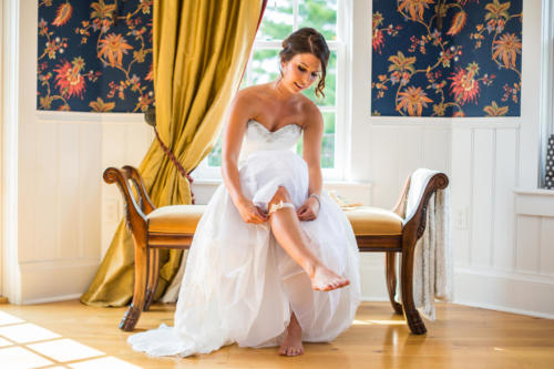 bride putting on her shoes in the queens retreat in the copperstone inn in rockton illinois