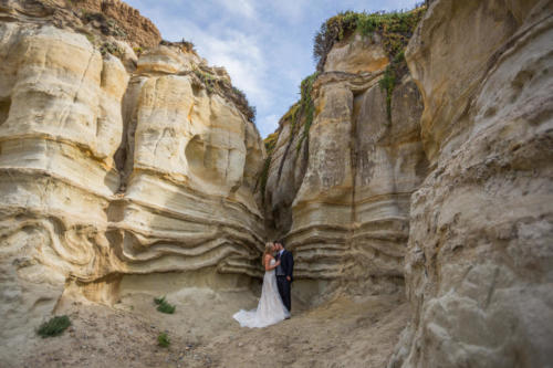 bride and groom in sandstone along the coast in california