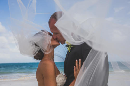 bride and groom under veil along the beach in mexico