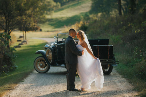 bride and groom kissing in front of classic car at oak hill in apple river illinois