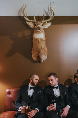 groomsmen under a mounted deer head.