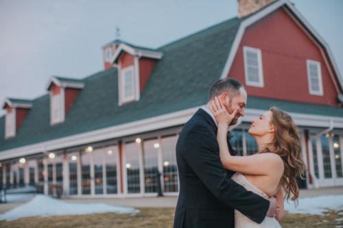 bride and groom in front of barn during a winter wedding