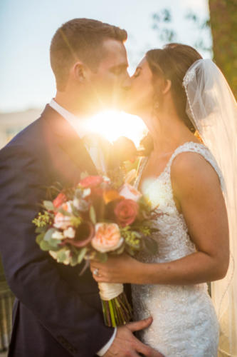 Bride and groom kissing with sunset in between them