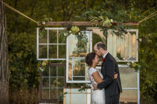 bride and groom kissing in front of vintage windows