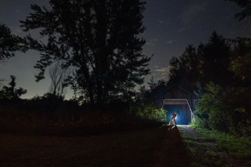 night time photograph of bride and groom under a covered bridge