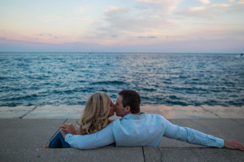 engaged couple kissing along lake Michigan at sunset