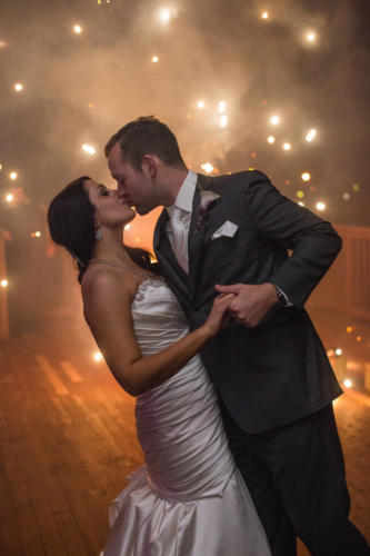 bride and groom kissing with fireworks behind them