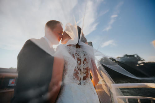 bride and groom kissing on boat in the rock river in rockford illinois