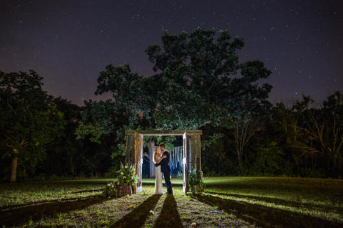 night time photograph under the stars with bride and groom