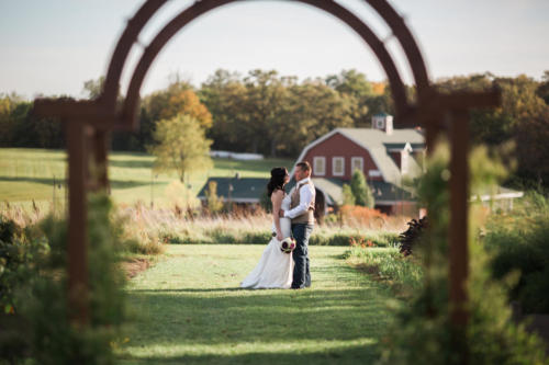 bride and groom under arch at Orchard Ridge Farms the Pavilion in Rockton Illinois