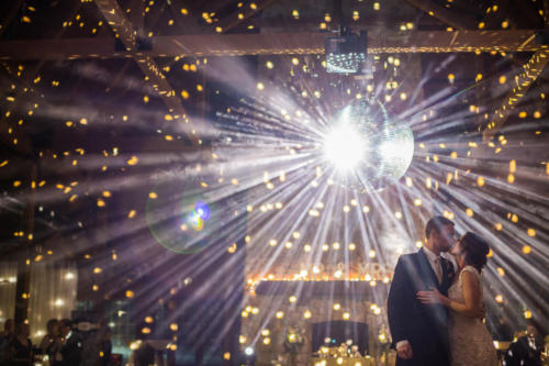 bride and groom first dance under a huge disco ball