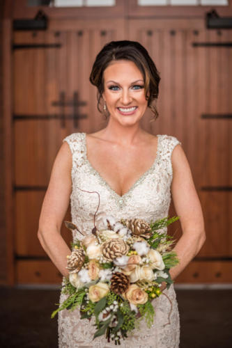 bride with winter wedding bouquet with pine cones